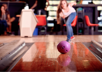 girl throwing a purple bowling ball down the lane during the unlimited bowling special