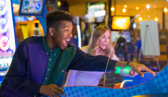 young adults smiling and playing arcade games