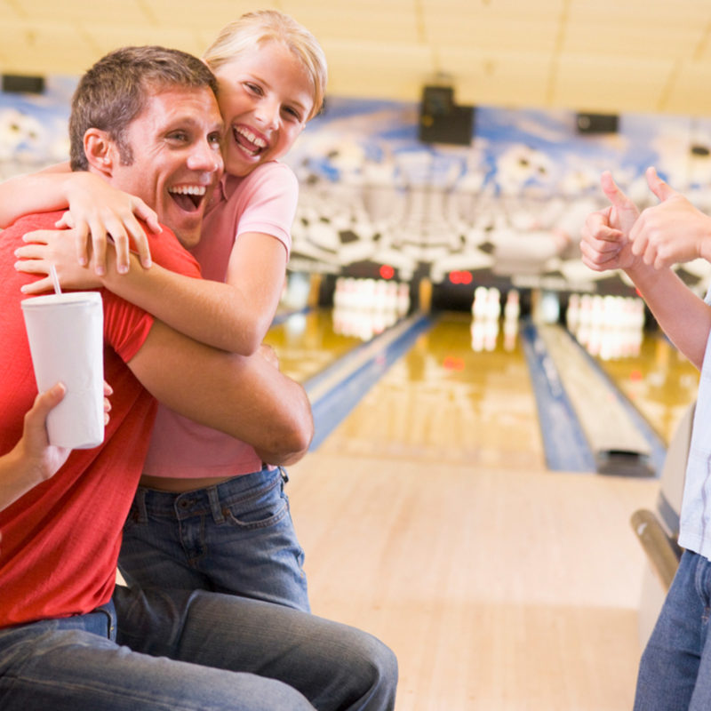 family celebrating at stars and strikes with the family fun package