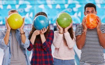 kids holding bowling balls in front of their faces during the 99 cent Wednesday special