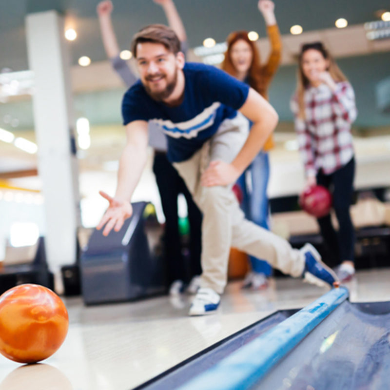 man bowling with an orange bowling ball with friends cheering behind him during the late night bowler's choice special