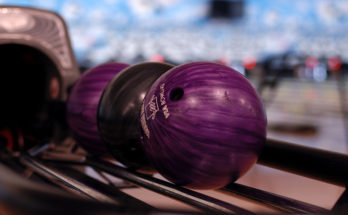 purple and black bowling balls on the rack for service industry night
