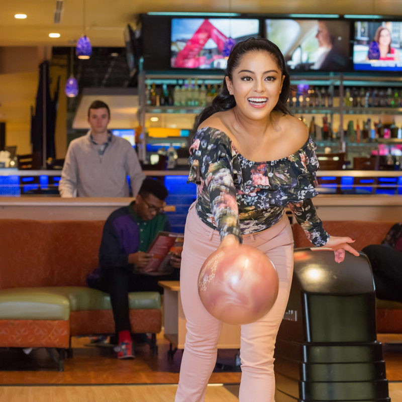 girl bowling with a dark pink bowling ball during the sunday morning bowling special
