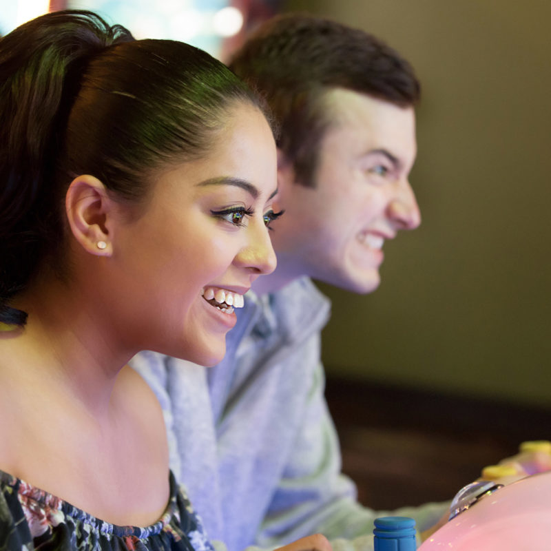 man and woman playing arcade games during unlimited play at stars and strikes