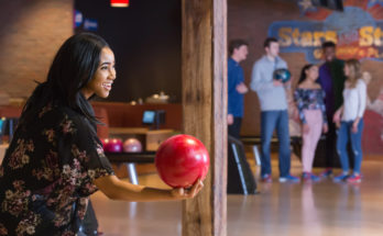 woman getting ready to bowl with a red bowling ball during ladies night