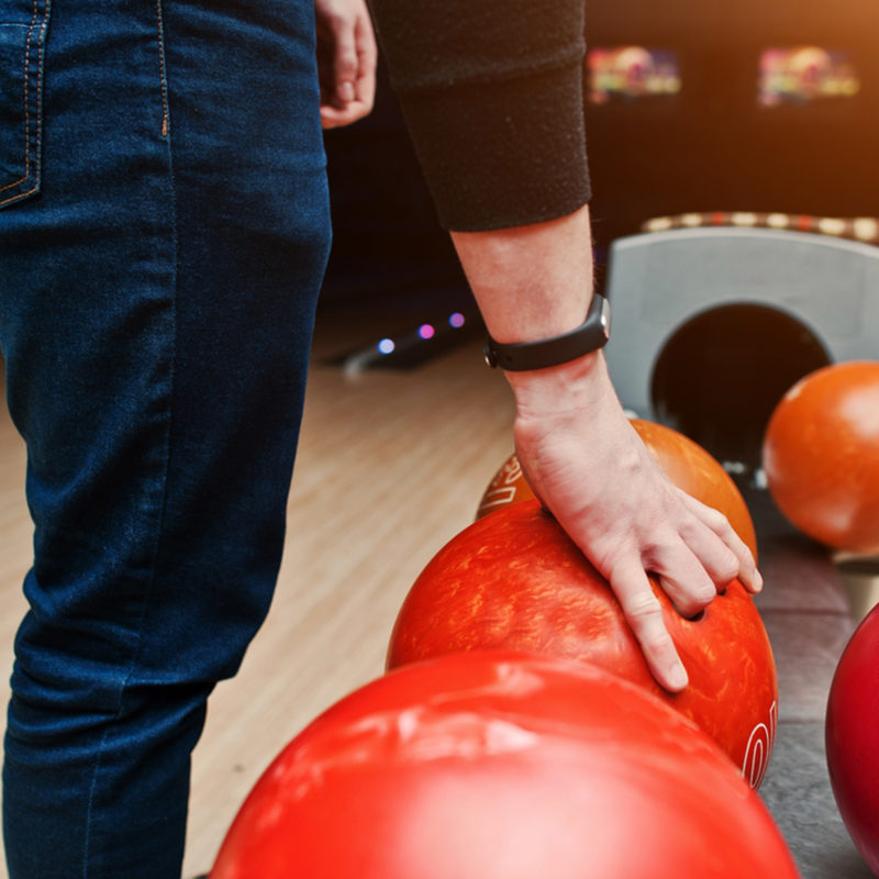 person picking up a red bowling ball
