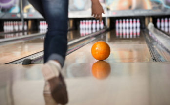 orange bowling ball rolling down lane during a game in stars and strikes bowling leagues