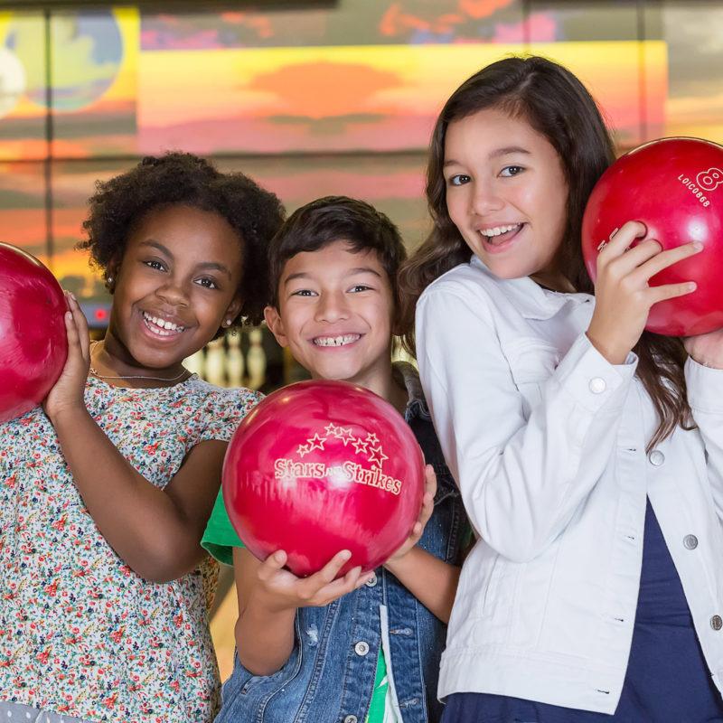 kids smiling holding red bowling balls