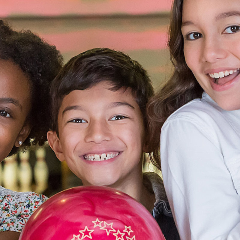 kids smiling holding red bowling balls