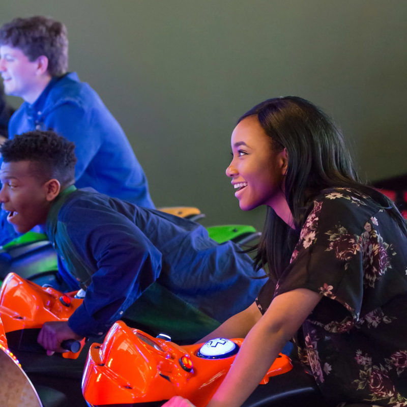 young adults playing motorcycle arcade game and enjoying specials at stars and strikes