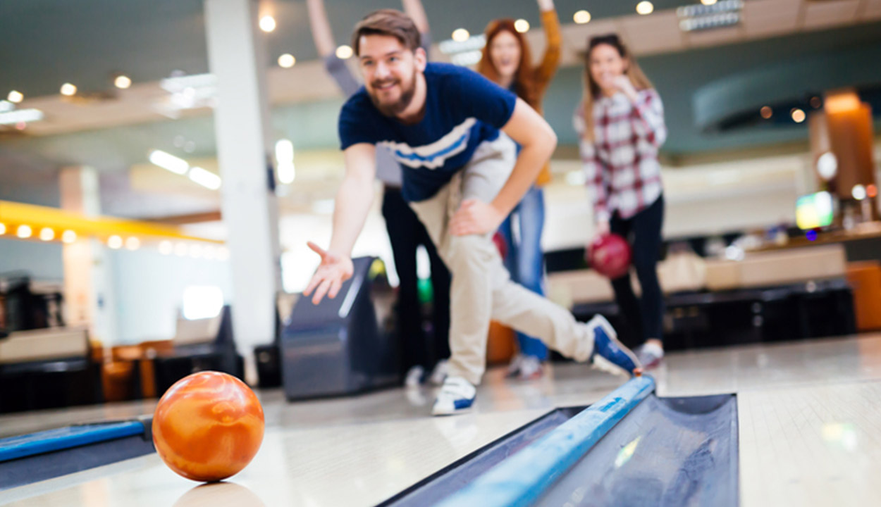 young adult bowling an orange ball down the lane during a team building exercise
