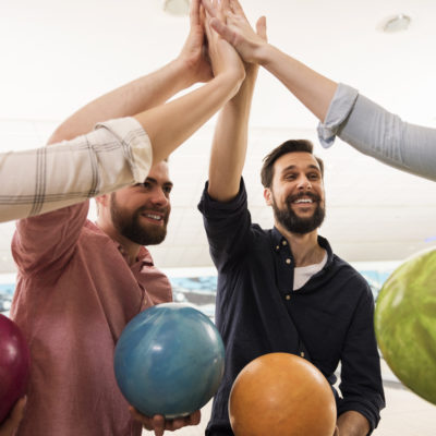 group high five while holding bowling balls