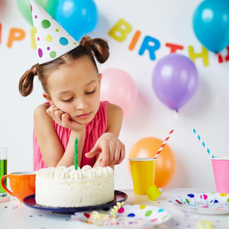 Sad little girl sitting table for her birthday