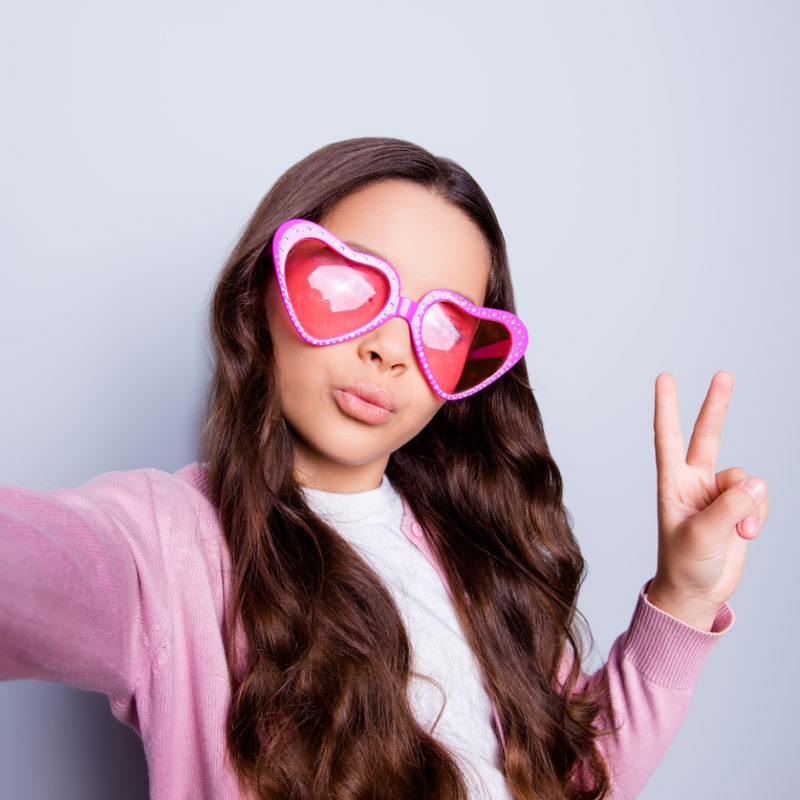 Tween girl taking a selfie while making peace sign and heart-shaped sunglasses