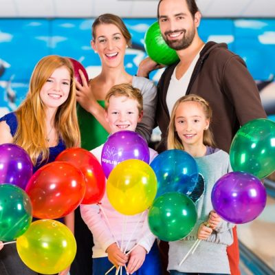 family with balloons at a birthday party venue