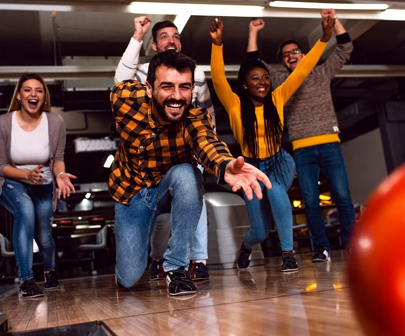Guy Bowling with Left Hand with Friends