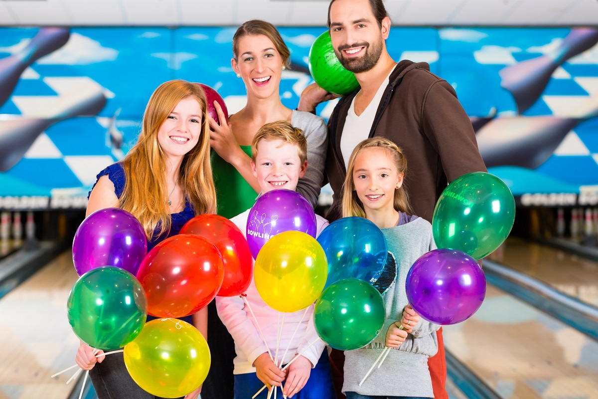 Family Holding Birthday Balloons in front of Bowling Lane