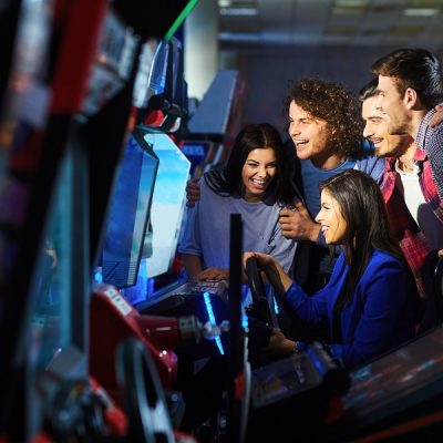 Group of Friends Play Racing Game at Arcade